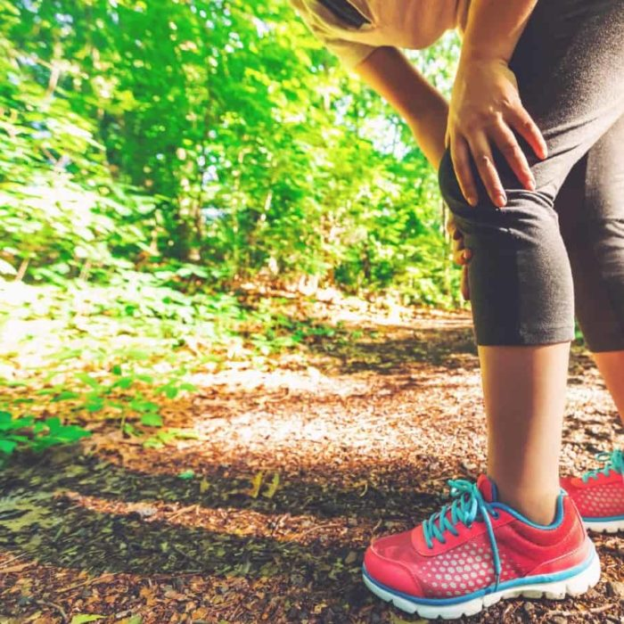 Woman in running shoes on a trail holding her knee in pain