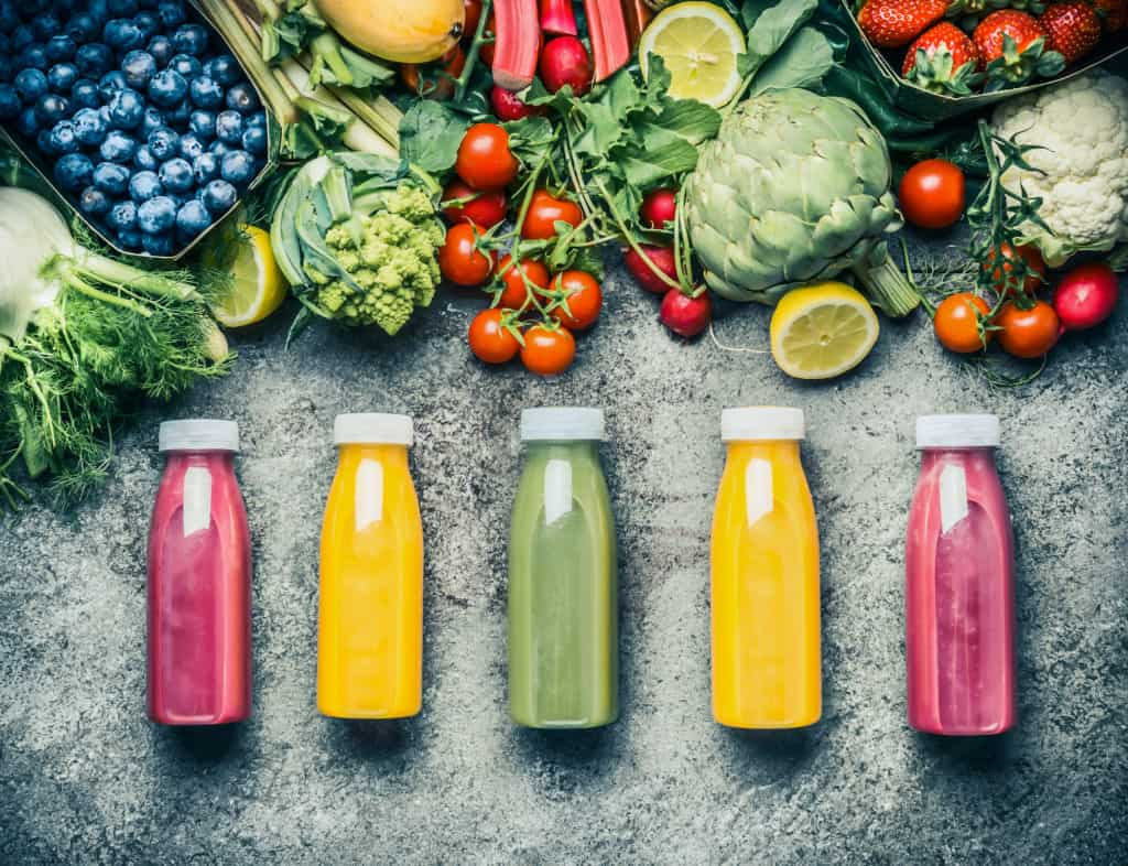 5 bottles of colorful fresh juice surrounded by fresh fruits and vegetables