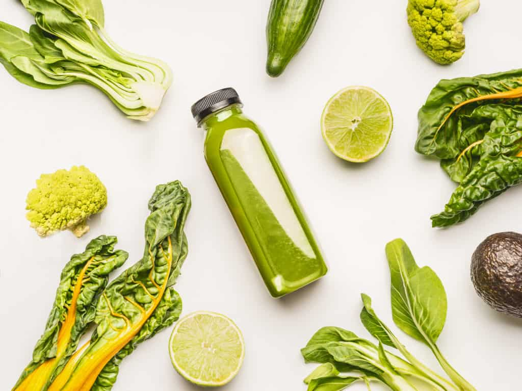Plastic bottle filled with green juice lays on its side on a white table surrounded by leafy green vegetables