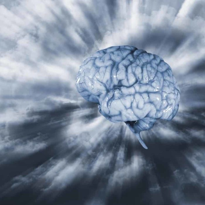 A brain floating in the sky with light emitting from it