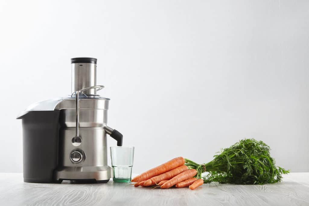 Centrifugal juicer ready to make carrot juice sitting on a wood table, fresh carrots lay on the wooden table