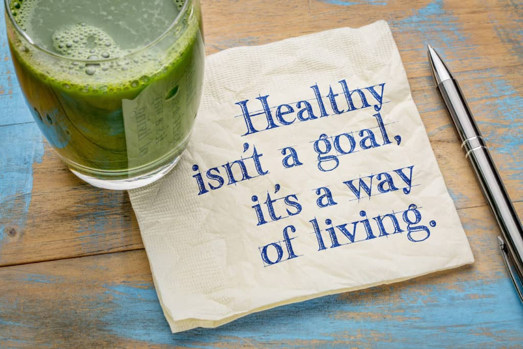 Healthy is not a goal, it is a way of living advice or reminder - handwriting on a napkin with a glass of fresh, green, vegetable juice