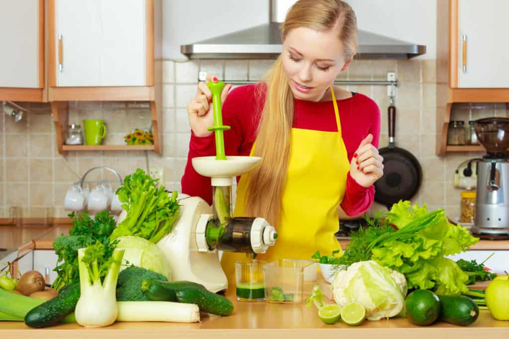 Woman making green juice with a masticating juicer, surrounded by vegetables