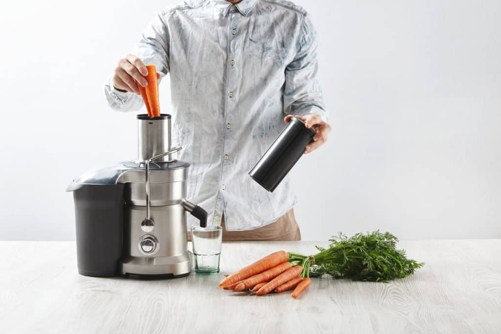 Man putting carrots into a Centrifugal juicer on a wood countertop, fresh carrots lay on wooden table