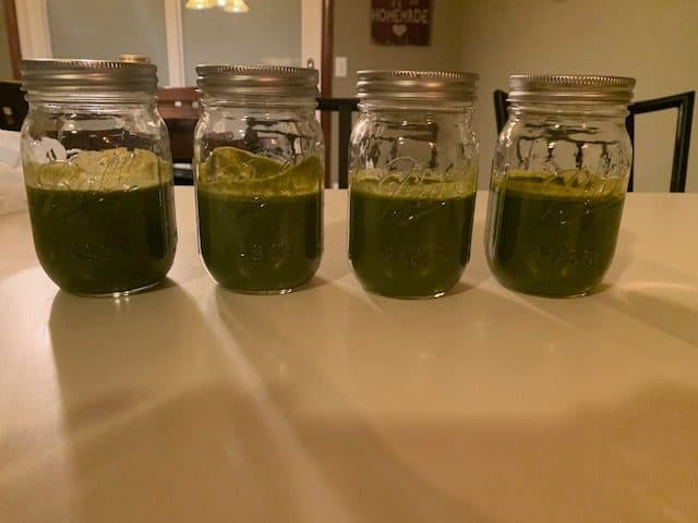 4 Mason jars sitting on a white counter filled with green juice