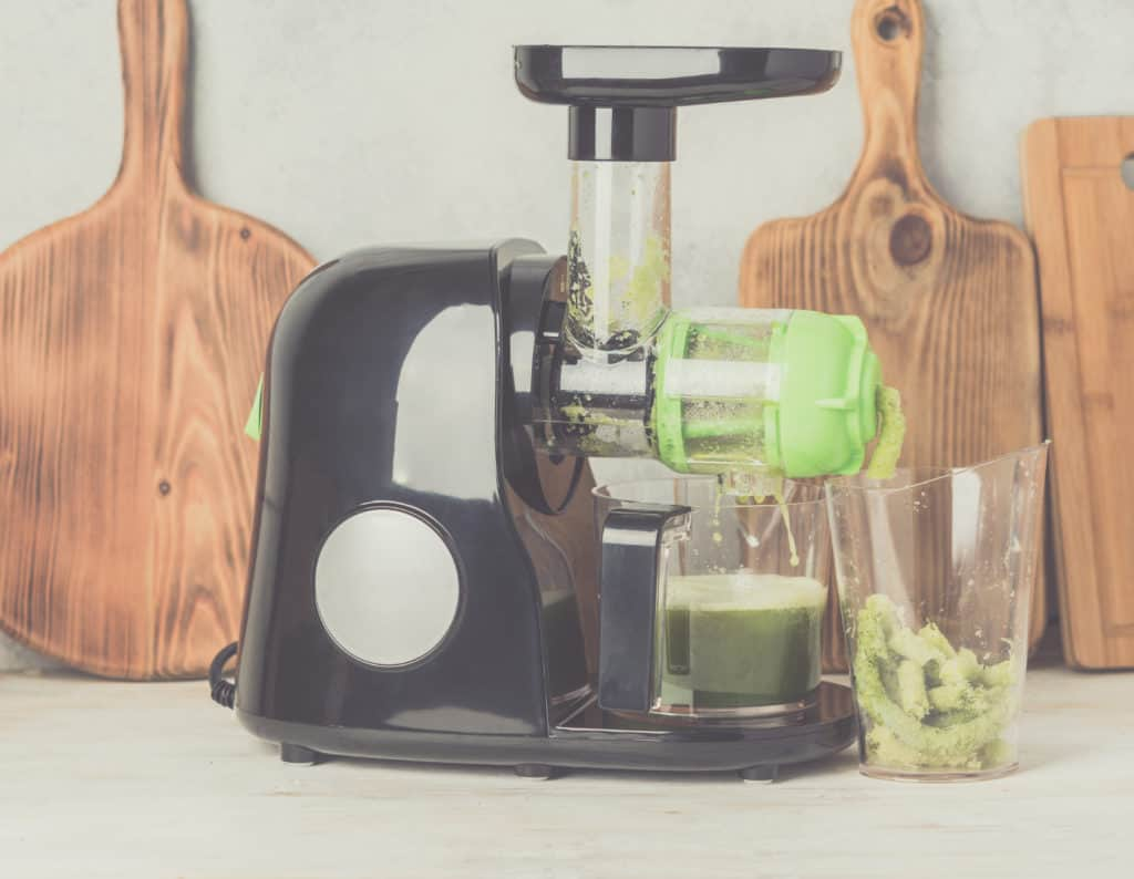 Masticating juicer making green juice sitting on a white table with wooden cutting boards in the background