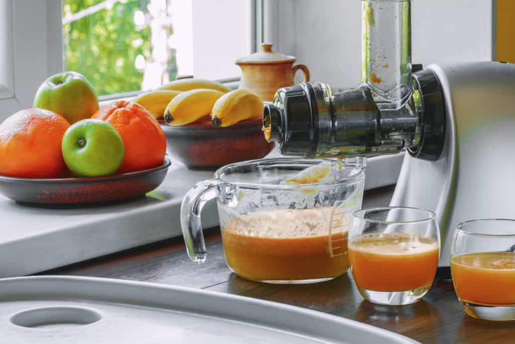 Horizontal masticating juicer on a wooden table making fresh carrot juice