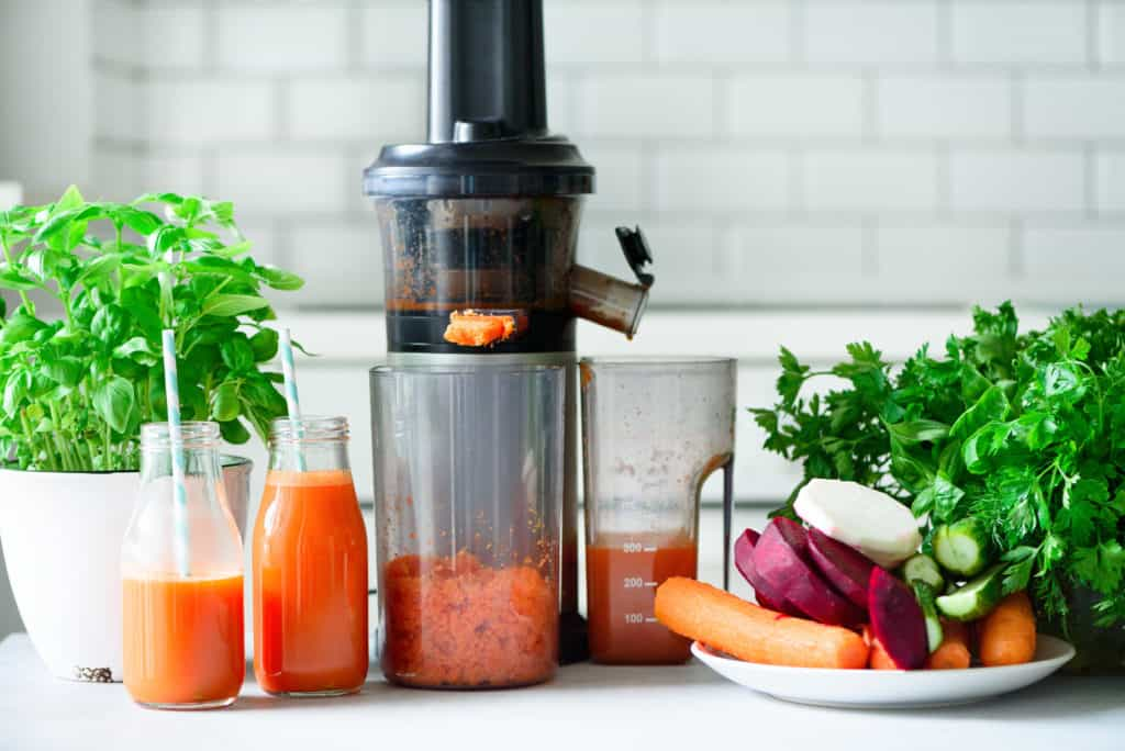 Vertical masticating juicer making carrot juice on a white countertop, surrounded by fresh vegetables and 2 bottles of carrot juice with straws