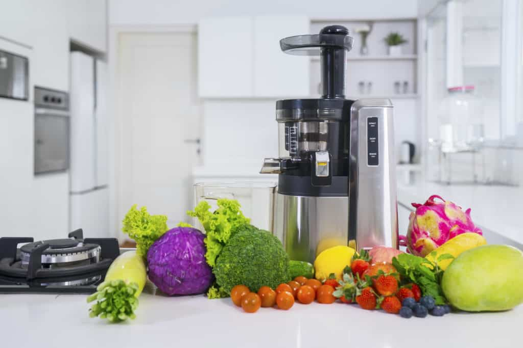 Vertical masticating juicer on counter surrounded by fruits and vegetables